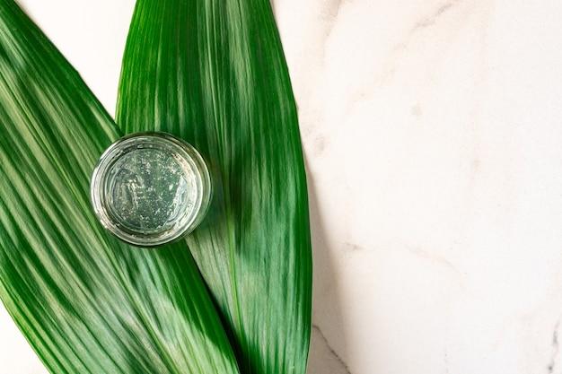 Прозрачный гель с текстурой пузырьков в прозрачной банке на мраморной поверхности