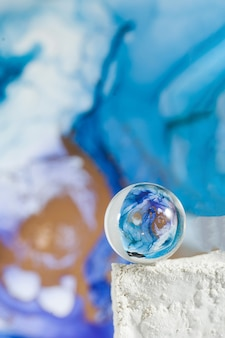 A transparent glass ball on an abstract blue background the technique of alcoholic ink