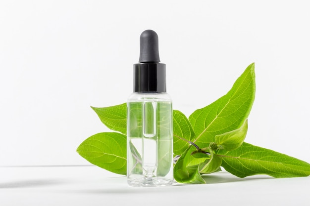 Transparent glass bottle with a dropper with moisturizer on a white background. natural cosmetic face serum with hyaluronic acid with green leaves
