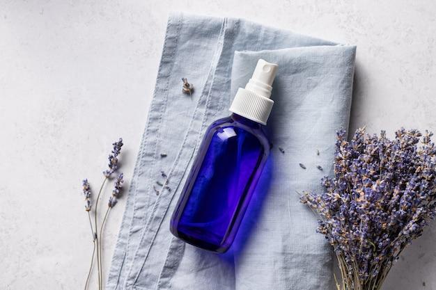 Transparent glass bottle with lavender spray, plants, kitchen cloth on light cement background