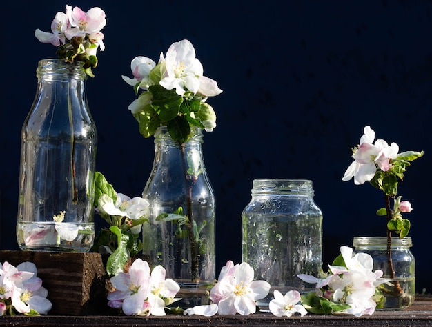투명한 유리병과 물과 사과나무 꽃이 든 항아리는 떨어지는 물방울 아래 소박한 나무 탁자 위에 있습니다. 어두운 배경입니다. 카피스페이스