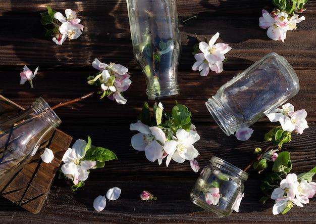 Прозрачные стеклянные бутылки и банки с водой и цветами яблони на деревенской деревянной столешнице под падающими каплями воды. темный фон. плоская планировка. вид сверху