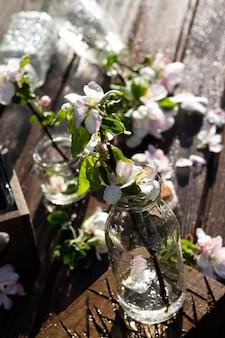 투명한 유리병과 물과 사과나무 꽃이 든 항아리는 떨어지는 물방울 아래 소박한 나무 탁자 위에 있습니다. 어두운 배경입니다. 수직의