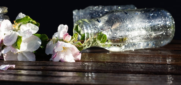 Transparent glass bottles and jars with water and apple tree flowers on a rustic wooden tabletop under falling drops of water. dark background. copyspace