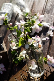 Transparent glass bottles and jars with water and apple tree flowers on a rustic wooden tabletop under falling drops of water. dark background. vertical
