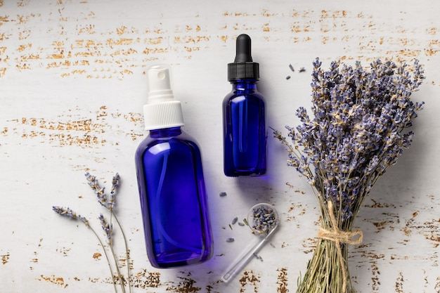 Transparent glass bottles with lavender spray and plants on wood background