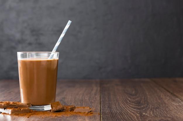 Transparent glass of chocolate milkshake with straw