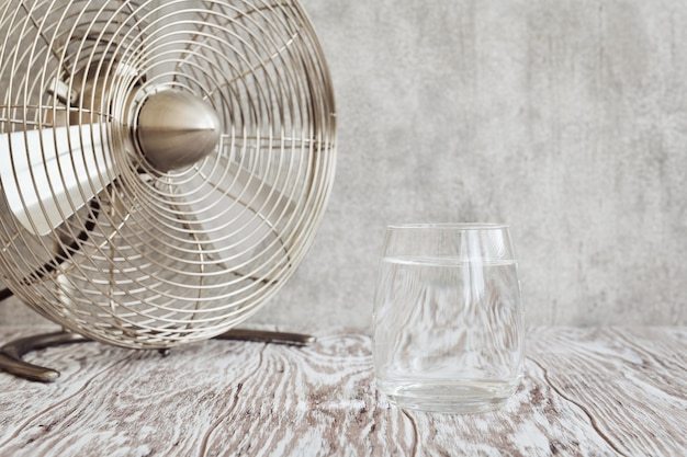 Transparent glass of clear water and a small table fan on a wooden table closeup, shallow depth of field