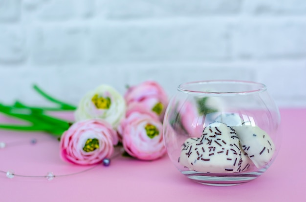 Transparent glass jar with cookies in heart shape and flowers on pink background.