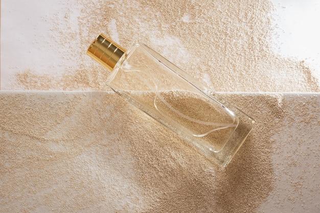 Прозрачный стеклянный флакон духов с золотой крышкой на фоне песка
