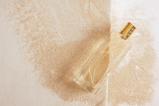 Прозрачный стеклянный флакон духов с золотой крышкой с этикеткой на песчаном фоне, копия пространства, вид сверху, макет косметической концепции