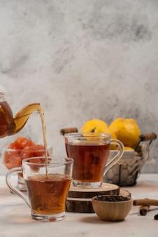 La teiera di vetro trasparente versa il tè nella tazza di vetro sul tavolo di marmo.