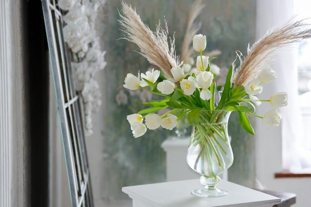 Прозрачная стеклянная ваза с букетом цветов тюльпанов