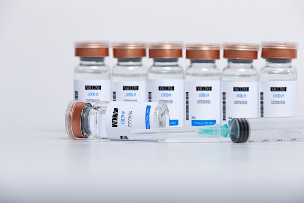 Прозрачные стеклянные флаконы с вакциной covid-19 и шприц