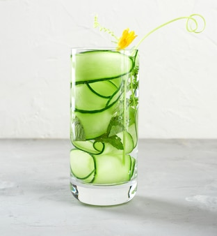 Transparent glass with cucumber pieces, mint leaves and mineral water, healthy lifestyle, detox
