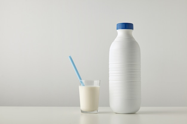Transparent glass with fresh milk and blue drinking straw inside near plastic riffled blank bottle with blue cap