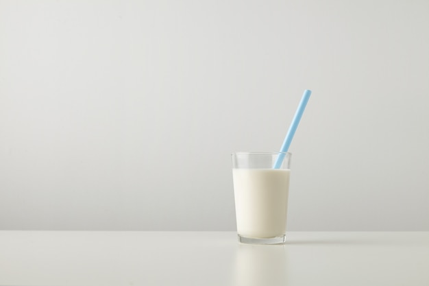 Transparent glass with fresh organic milk and blue drinking straw inside isolated on side of white table