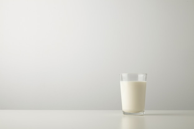 Transparent glass with fresh organic milk isolated on side of white table. space for your text above