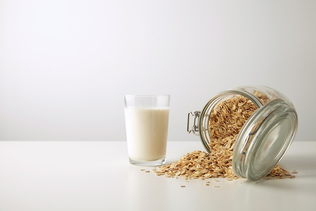 Transparent glass with fresh organic milk near lying half opened rustic jar with rolled oats spread out isolated in center on white table side view
