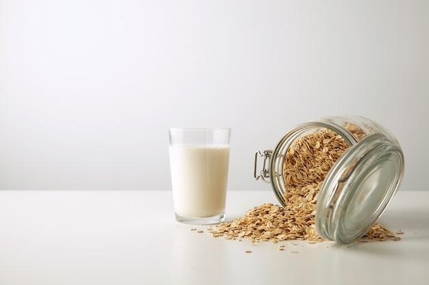 Прозрачное стекло со свежим органическим молоком рядом с лежащей наполовину открытой деревенской банкой с раскиданными овсяными хлопьями изолированно в центре на белом столе, вид сбоку