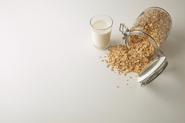 Прозрачное стекло со свежим органическим молоком рядом с лежащей открытой деревенской банкой с разложенными овсяными хлопьями изолированно в центре на белом столе, вид сбоку