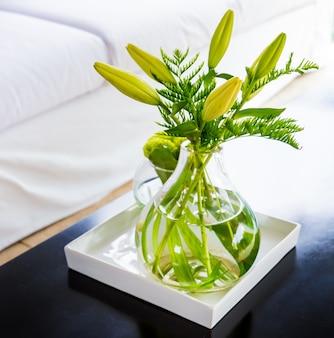 집에 실내 장식으로 배치된 녹색 꽃이 있는 투명한 유리