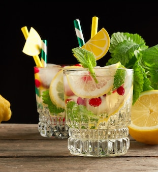 Transparent glass with lemonade and pieces of ice, red berries, a refreshing summer drink on a black space