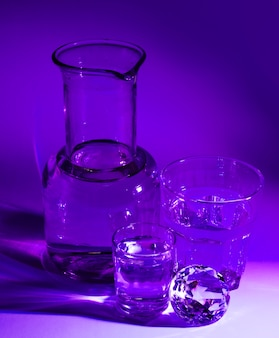 Transparent glasses of water; diamond and beaker on purple backdrop