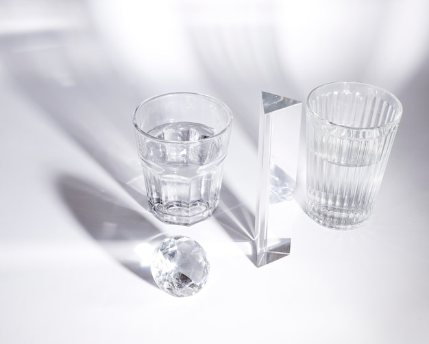 Transparent glasses of water; diamond and prism on white background with shadow