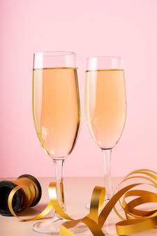 Прозрачные высокие бокалы для шампанского с праздничной золотой лентой на нежно-розовом