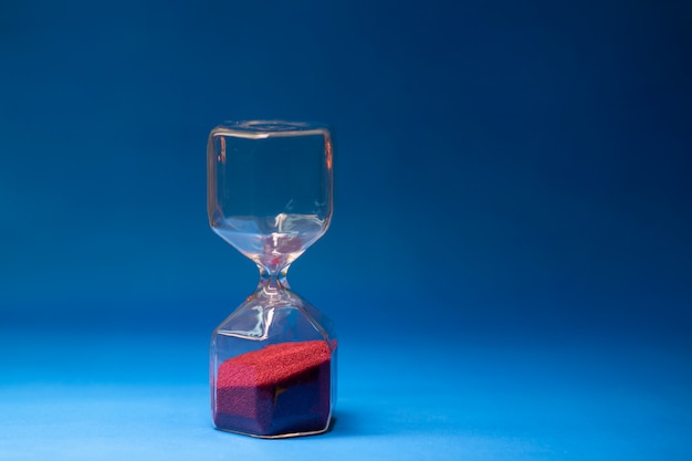 Transparent hourglass with red grains of sand located on a blue background with free space for text