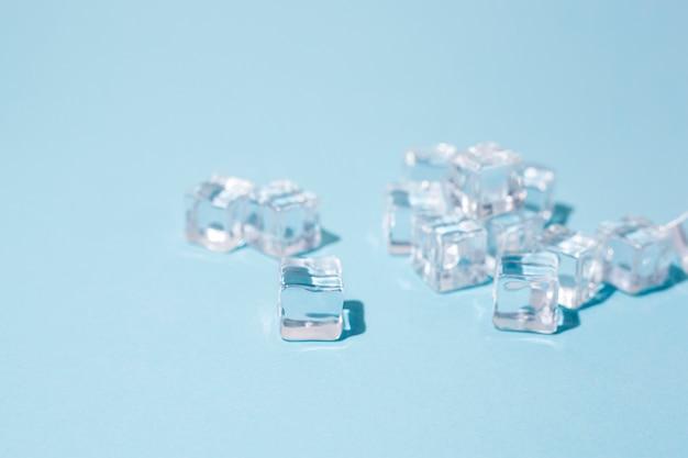 青い背景に透明な角氷。上面図、フラットレイ。