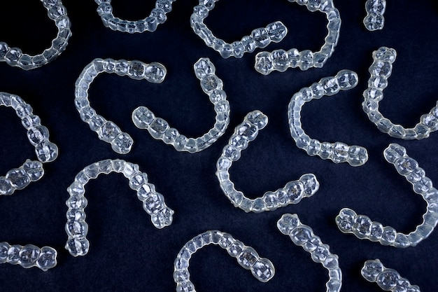 Transparent invisalign retainers brackets pattern on black background