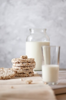 Transparent jar and glass of milk, wholegrain crisp bread on a wooden table