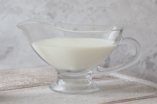 Transparent jug of milk on a wooden table on a gray