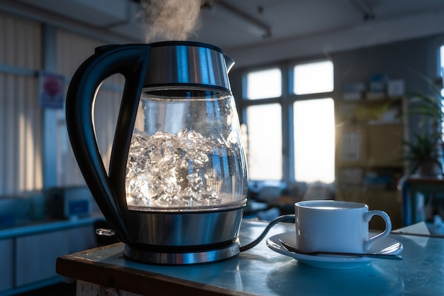 A transparent kettle of water boils against the of the sunset shining through the window