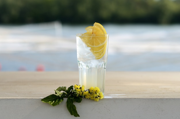 Transparent lemonade with ice and lemon in a glass beaker. with flower decor