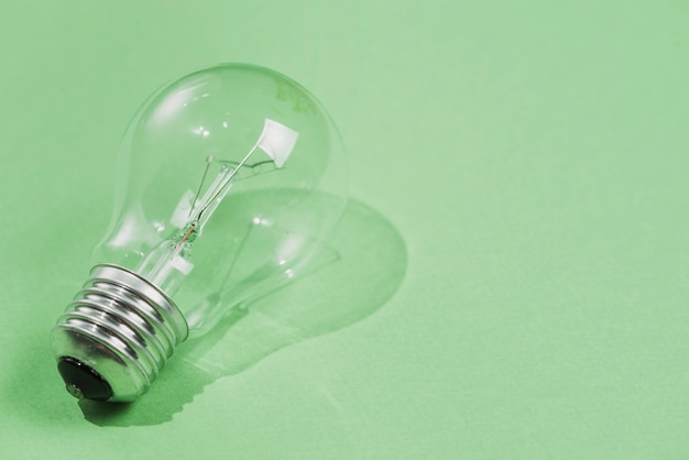 Transparent light bulb on green background