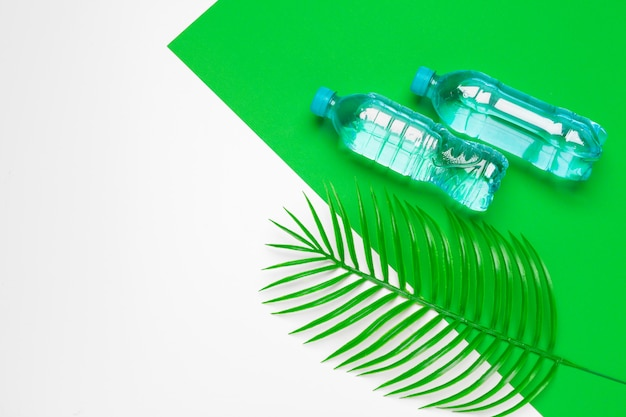 Transparent liquid bottle with tropical palm leaves, top view background