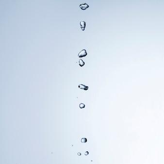 Gocce di liquido trasparente su sfondo chiaro