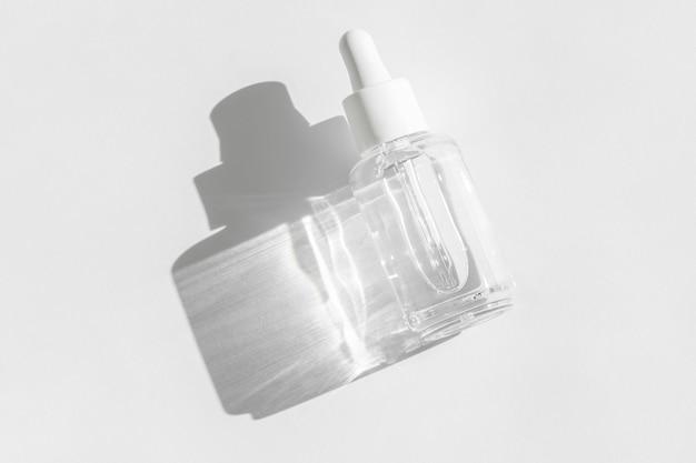 Прозрачная упаковка жидких продуктов в стеклянной бутылке. сыворотка против старения с коллагеном и пептидами