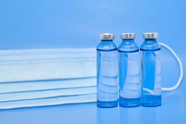 水色の背景に透明な医療用アンプルと保護用医療用マスク。
