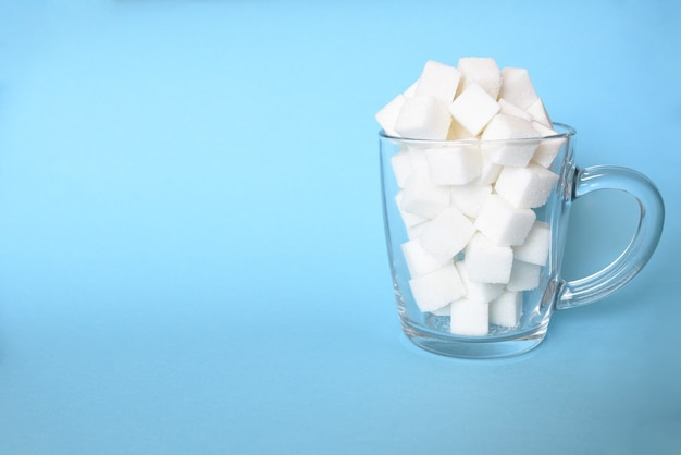 Transparent mug full of refined white sugar cubes on blue background. copy space