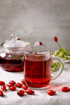 Transparent mug of rose hip berries herbal tea and glass teapot standing on white linen table cloth with wild autumn berries around. healthy hot drink.