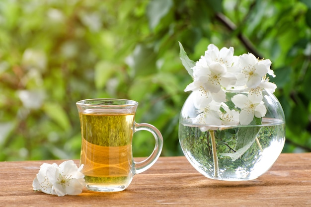Transparent mug of tea and a vase with jasmine on a wooden table