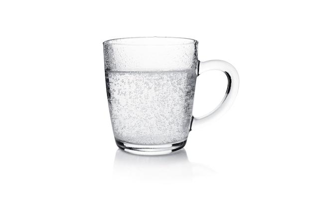 白で隔離された泡立つ水と透明なマグカップ。