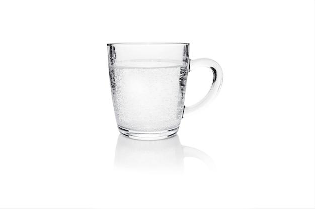 白で隔離された発泡性の水と透明なマグカップ。