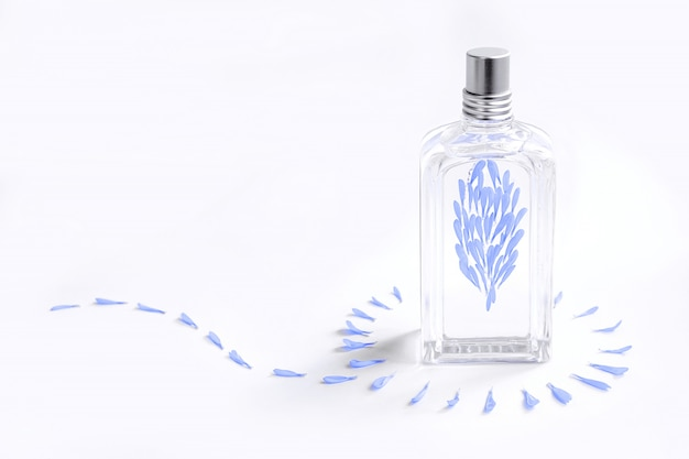 Transparent perfume bottle on white decorated with blue flower petals