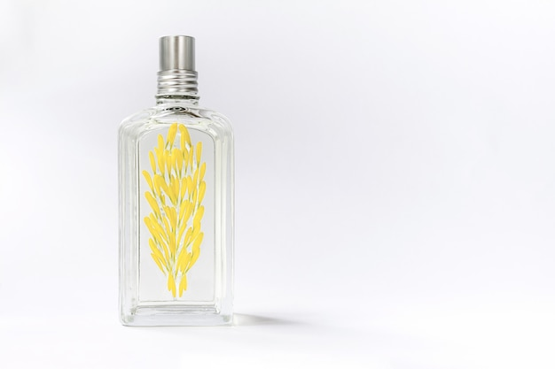 Transparent perfume bottle on white decorated with yellow flower petals