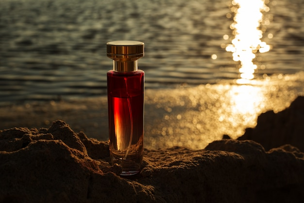 Transparent perfume bottles against the evening sunset. male beauty concept.